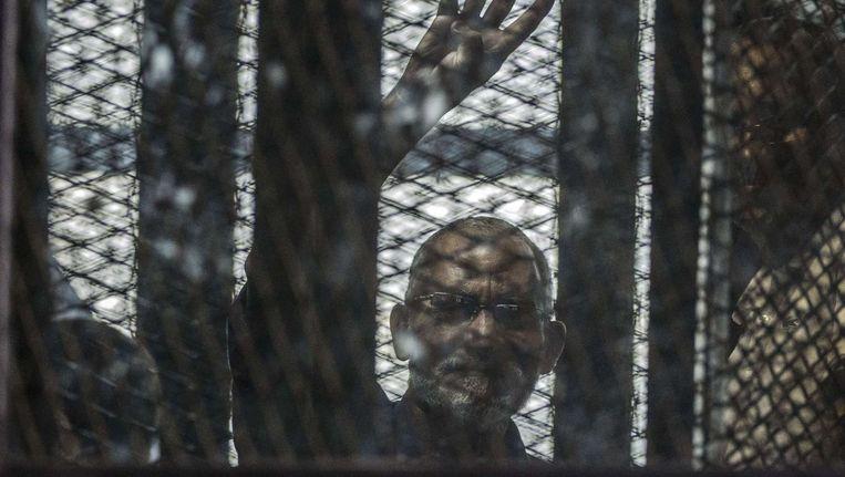 Mohamed Badie, leider van de Broederschap, zwaait vanuit een kooi in de rechtbank. Beeld afp