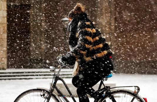 Een fietser heeft het zwaar in de sneeuw.