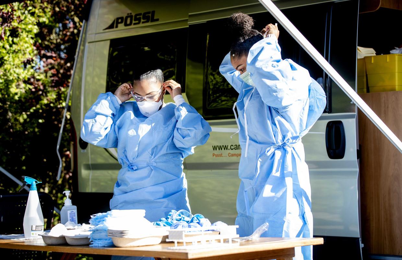 GGD-personeel treft voorbereidingen om zorgpersoneel te testen op het coronavirus bij een mobiele testlocatie in de vorm van een camper.  Beeld ANP