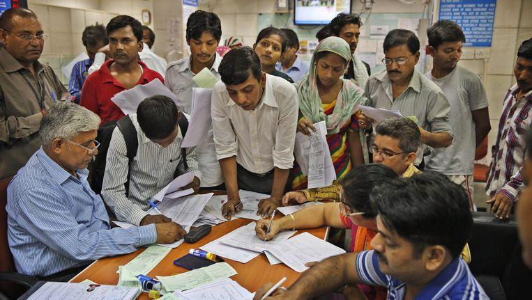 Bij een staatsbank de hoofdstad Delhi komen mensen hun formulieren inleveren waarmee ze een bankrekening kunnen aanvragen. Beeld ap