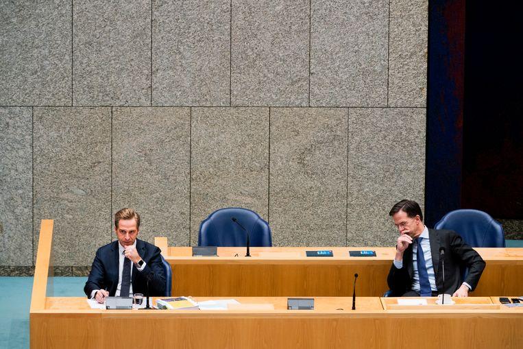 Links Minister Hugo de Jonge van Volksgezondheid, Welzijn en Sport (CDA) en rechts premier Mark Rutte tijdens het Tweede Kamerdebat over de ontwikkelingen rond het coronavirus. Beeld Foto Freek van den Bergh / de Volkskrant
