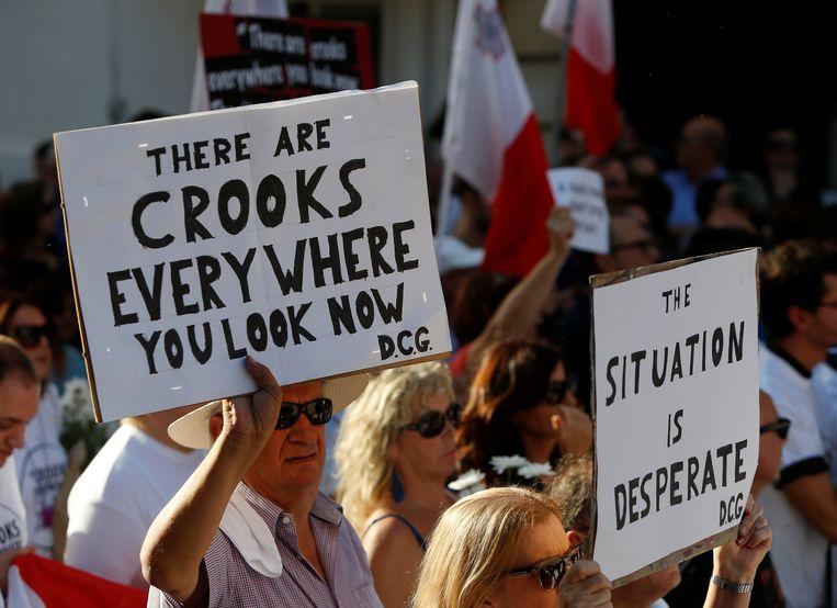 Mensen houden borden omhoog met de laatste gepubliceerde woorden van onderzoeksjournalist Daphne Caruana Galizia, die in oktober vorig jaar vermoord werd.