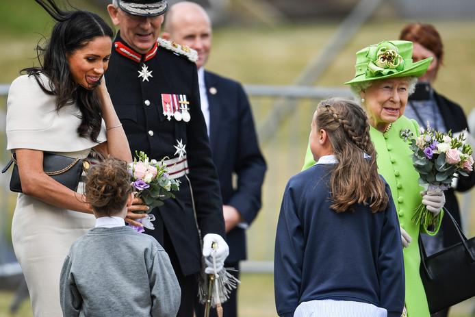 Queen Elizabeth II en Meghan  krijgen een bloemetje.