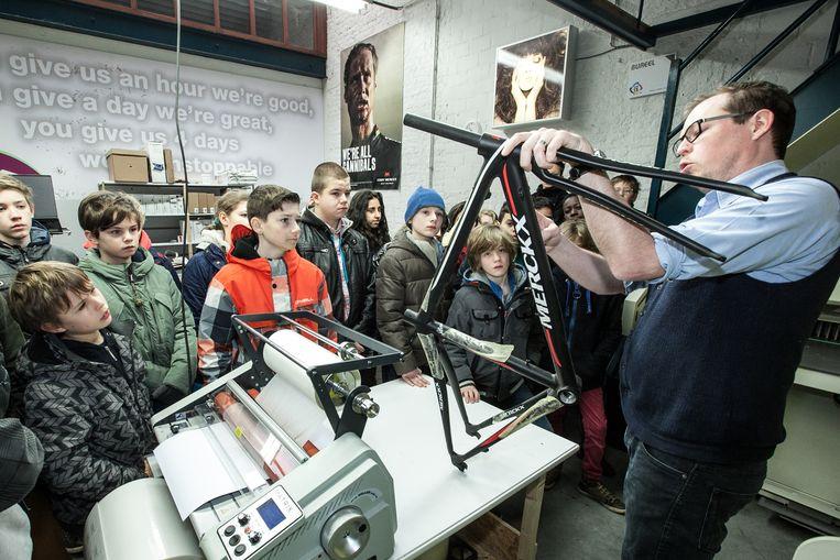 De kinderen leren onder andere hoe men foto's en stickers drukt, zoals op een Eddy Merckx-fiets op de techclass bij DOK13.
