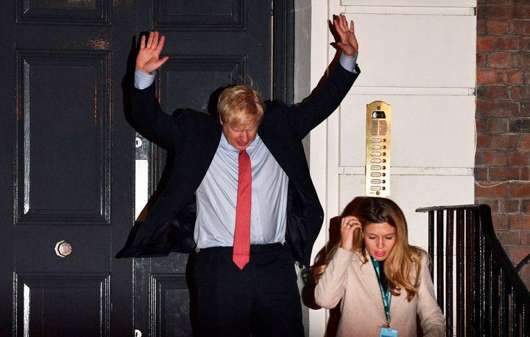 Boris Johson steekt zijn handen in de lucht op het moment dat hij partijbureau van de Conservatieven verlaat. De Conservatieven hebben een ruime meerderheid behaald in het Lagerhuis. Beeld null