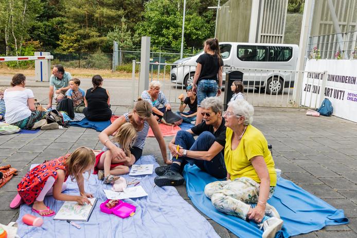 Een busje verlaat vrijdag het detentiecentrum in Zeist terwijl demonstranten waken bij de poort.