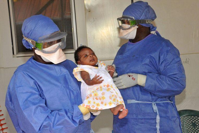Artsen in Guinee met een jonge ebola-patiënt. Beeld afp