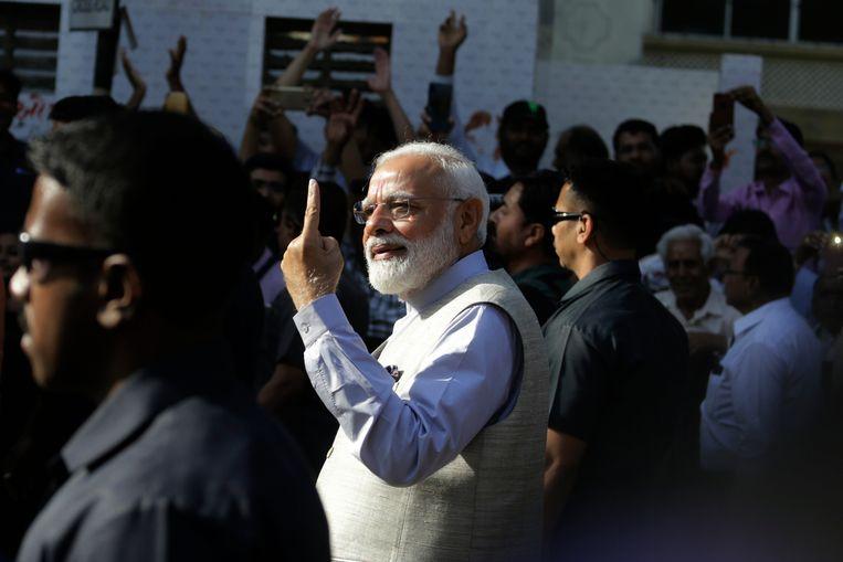 Premier Narendra Modi toont de inktvlek op zijn vinger, die bewijst dat hij heeft gestemd. Beeld AP