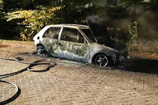 Een uitgebrande auto in de Pater Wolffstraat in Culemborg.