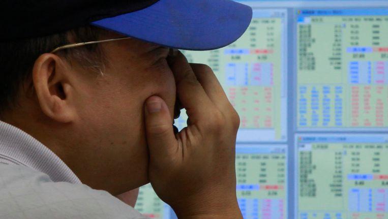 Een beurshandelaar in Hongkong wrijft zijn ogen uit. Beeld EPA