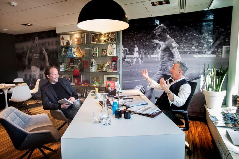 Schrijver Michel van Egmond (links aan tafel) met spelersmakelaar Rob Jansen, het onderwerp van zijn nieuwe boek. Beeld Werry Crone