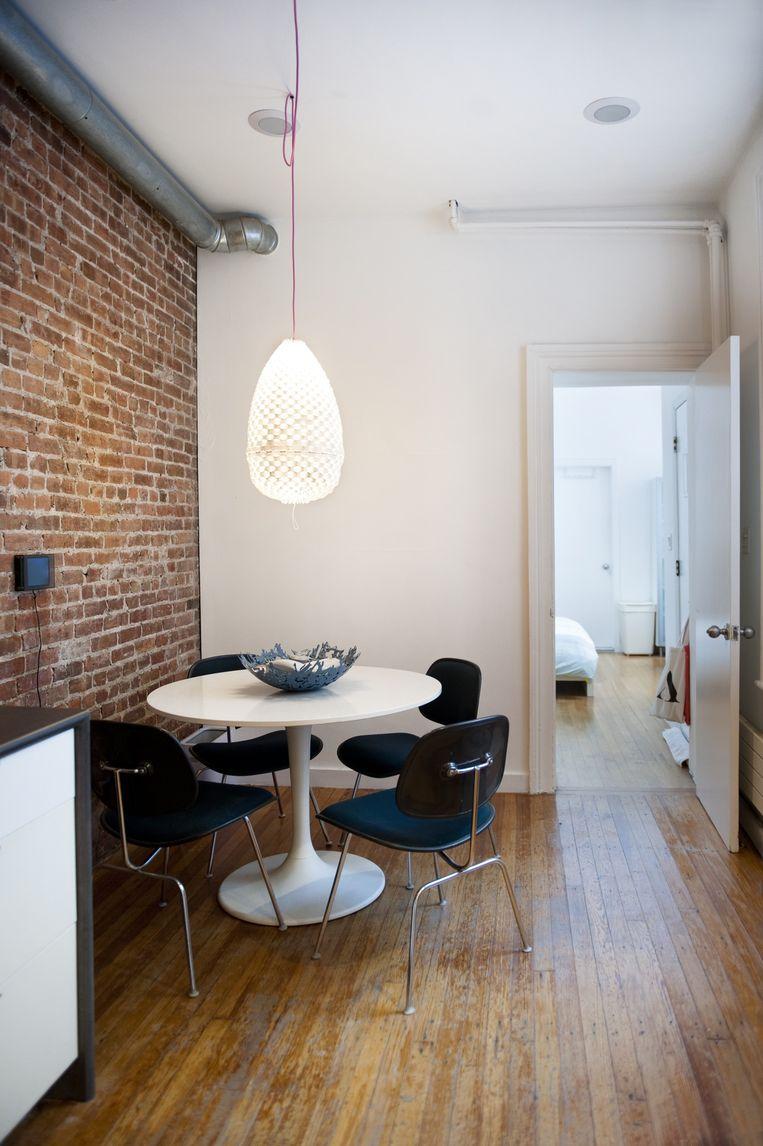 De ronde eettafel is een replica van de beroemde Saarinen tafel, de stoelen zijn van Eames. Jan: 'Helaas hebben we het geld nog niet om de 'echte' te kopen. Bovendien staat dit model perfect bij de lamp Trianon van Paula Arntzen.' Beeld Els Zweerink