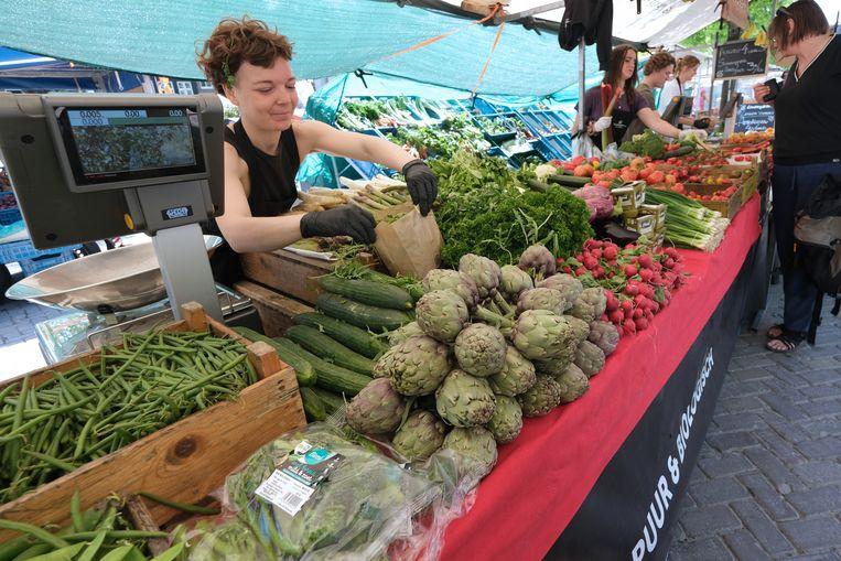 Een vrouw op de Amsterdamse  Noordermarkt doet biologisch geteelde groente in een zak. De biologische landbouw moet over tien jaar een kwart van het geheel beslaan, in plaats van de tien procent die het nu is.  Beeld Getty