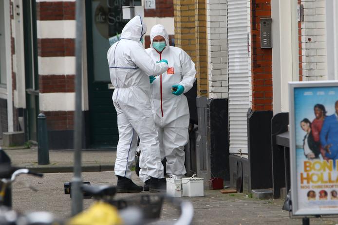 Medewerkers van de EOD halen twee handgranaten weg bij de waterpijpwinkel in Rotterdam-Delfshaven.