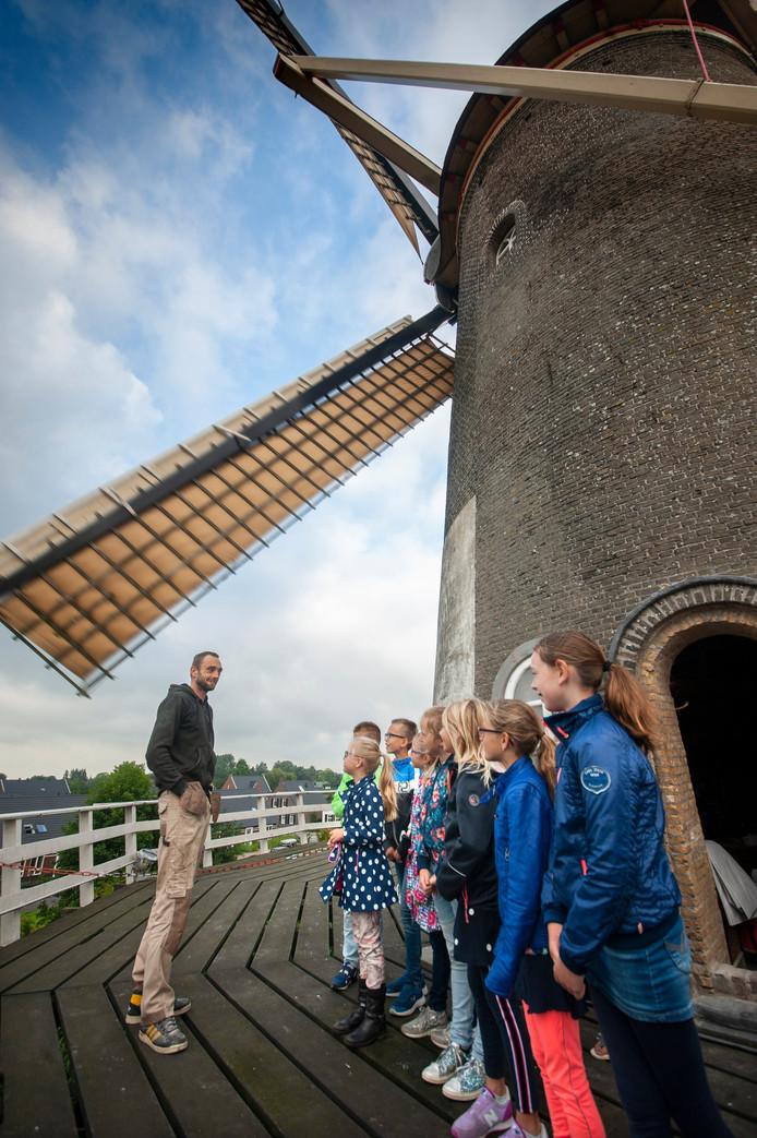 Molenaar Sven Verbeek legt aan de basisschoolleerlingen uit hoe een korenmolen werkt. ,,Hoeveel wordt er op een dag gemalen'', willen ze weten.