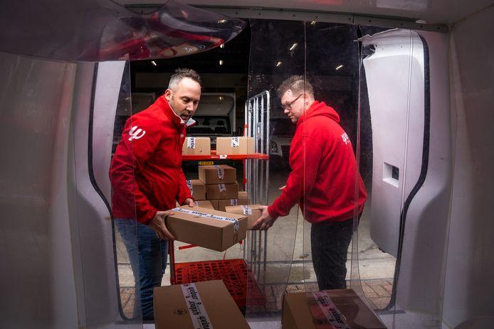 Roy Tinneveld laadt de bezorgauto, die ook bij de proefstraten wordt ingezet, met maaltijden vol. Kok Patrick Derks (rechts) helpt hem. Foto: Rolf Hensel.