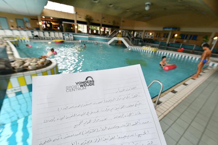Oldenzaal - Twee Syrische zwemmers bekijken de in Arabisch vertaalde huisregels voor het zwembad Vondersweijde