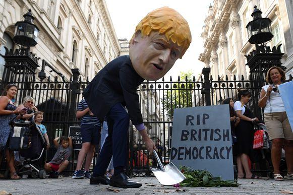 Een demonstrant met een Boris Johnson-masker op begraaft op symbolische wijze de Britse democratie aan de poort van Downing Street in Londen.
