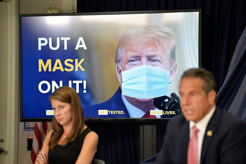 Tijdens een persconferentie over de coronacrisis van Andrew, de gouverneur van New York, wordt president Trump afgebeeld met een denkbeeldig mondkapje.