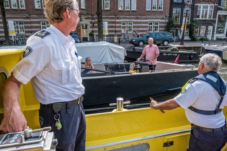 Rob, links en Alle, rechts, spreken een schipper aan die tegen het scheepsverkeer invoer op de Prinsengracht. Beeld Patrick Post