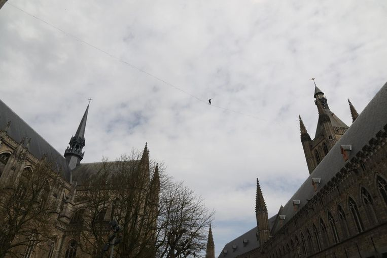 Een koorddanser, amper een stipje groot, wandelt op 60 meter hoogte tussen de Lakenhalle en de kathedraal.
