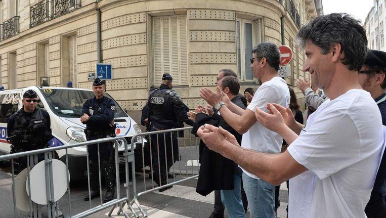 Demonstranten applaudisseren voor de politie, die het protest tegen de arbeidswet ondersteunt. Beeld afp