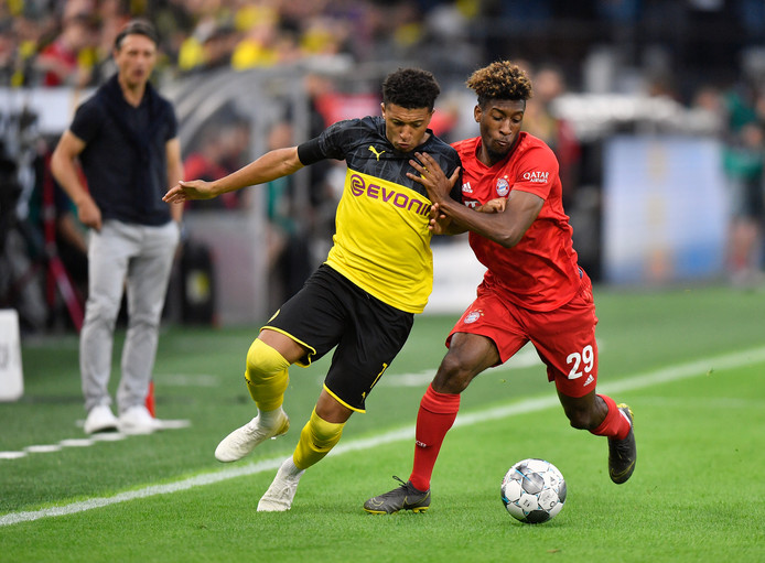 Kingsley Coman probeert Dortmund-aanvaller Jadon Sancho van de bal te zetten tijdens het duel om de Duitse Supercup.