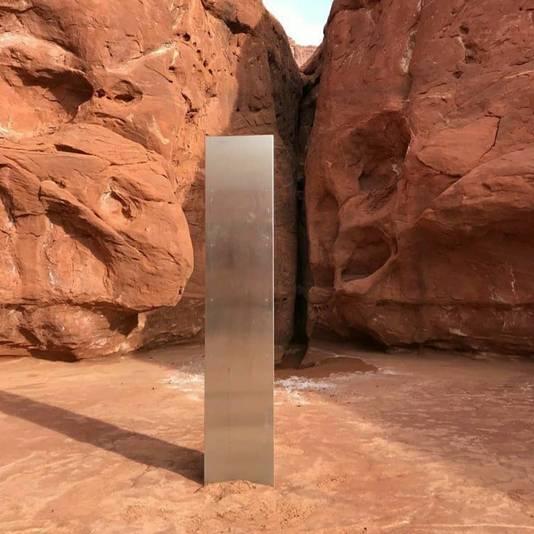 Een opvallend, glanzend voorwerp te midden van ruige rode rotsen in de woestijn van Utah.