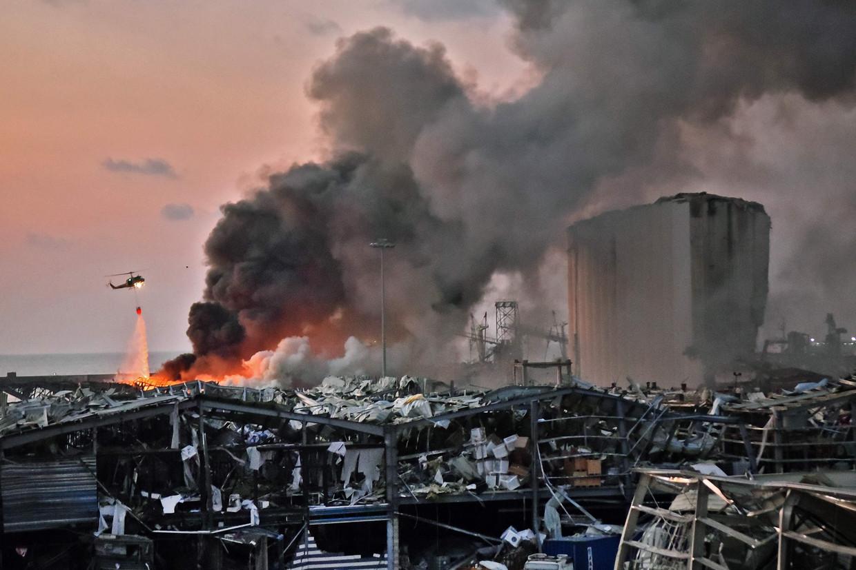 Een helikopter doet verwoede pogingen om een van de vele branden in de haven van Beiroet te blussen.