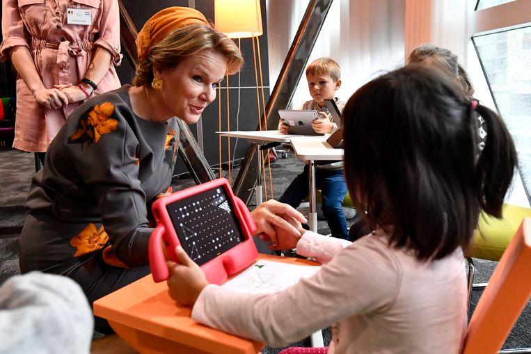 Koningin Mathilde spreekt met een kind dat een videogame speelt.