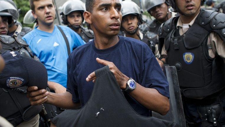 Een agent toont zijn kogelwerend vest nadat hij gisteren werd beschoten.