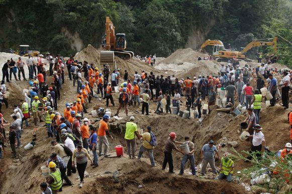Reddingswerkers en vrijwilligers verwijderen emmers modder van de locatie van de aardverschuiving, op zoek naar overlevenden.