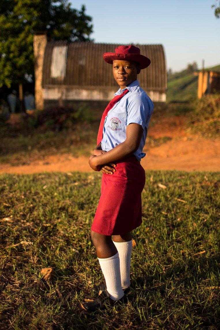 Een scholiere loopt naar huis over een theeplantage. Beeld Julius Schrank