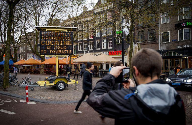 Toeristen worden op het Thorbeckeplein met een matrixbord gewaarschuwd voor de verkoop van witte heroïne. Beeld anp