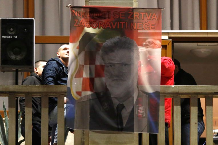 Bosnische Kroaten in het Bosnische Mostar hijsen een nationalistische vlag met een afbeeding van Praljak. Beeld AP