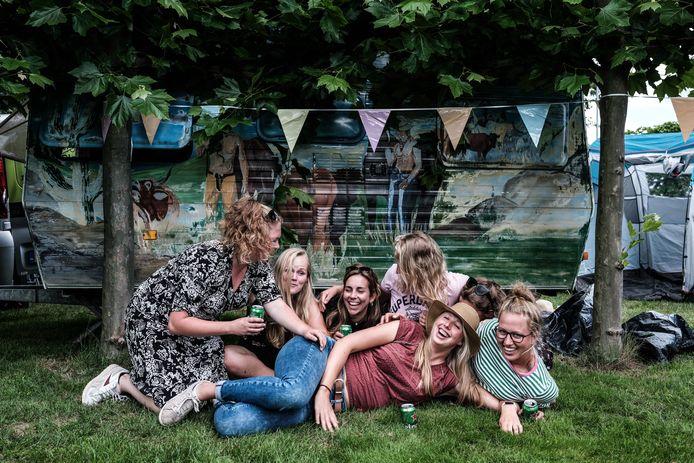 De meidengroep op hun kleine camping met de caravan.