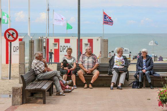 Enkele senioren op een bankje aan de Belgische kust.