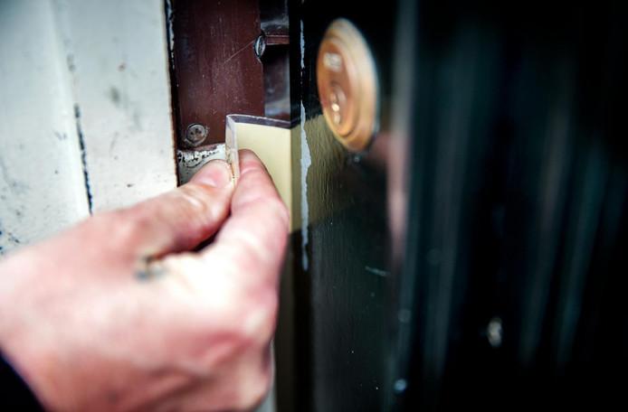 Archieffoto: demonstratie van hoe een inbreker zich toegang kan verschaffen tot een woning door ter hoogte van het deurslot iets tussen deur en kozijn te schuiven.   ANP XTRA JERRY LAMPEN