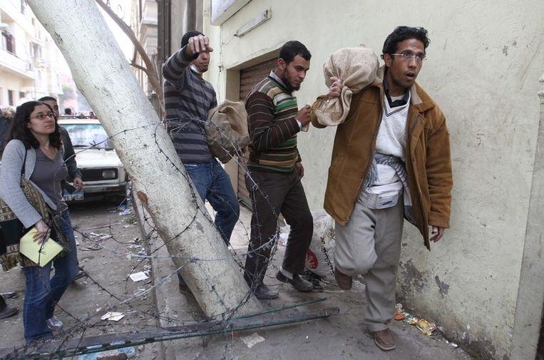 Egyptische betogers dragen zakken met stenen die naar de aanhangers van Mubarak gegooid kunnen worden. Beeld afp