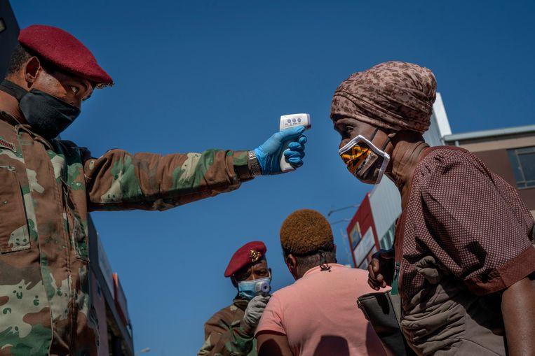 Een soldaat neemt de temperatuur op van een vrouw in één van de townships nabij Johannesburg.  Beeld AP