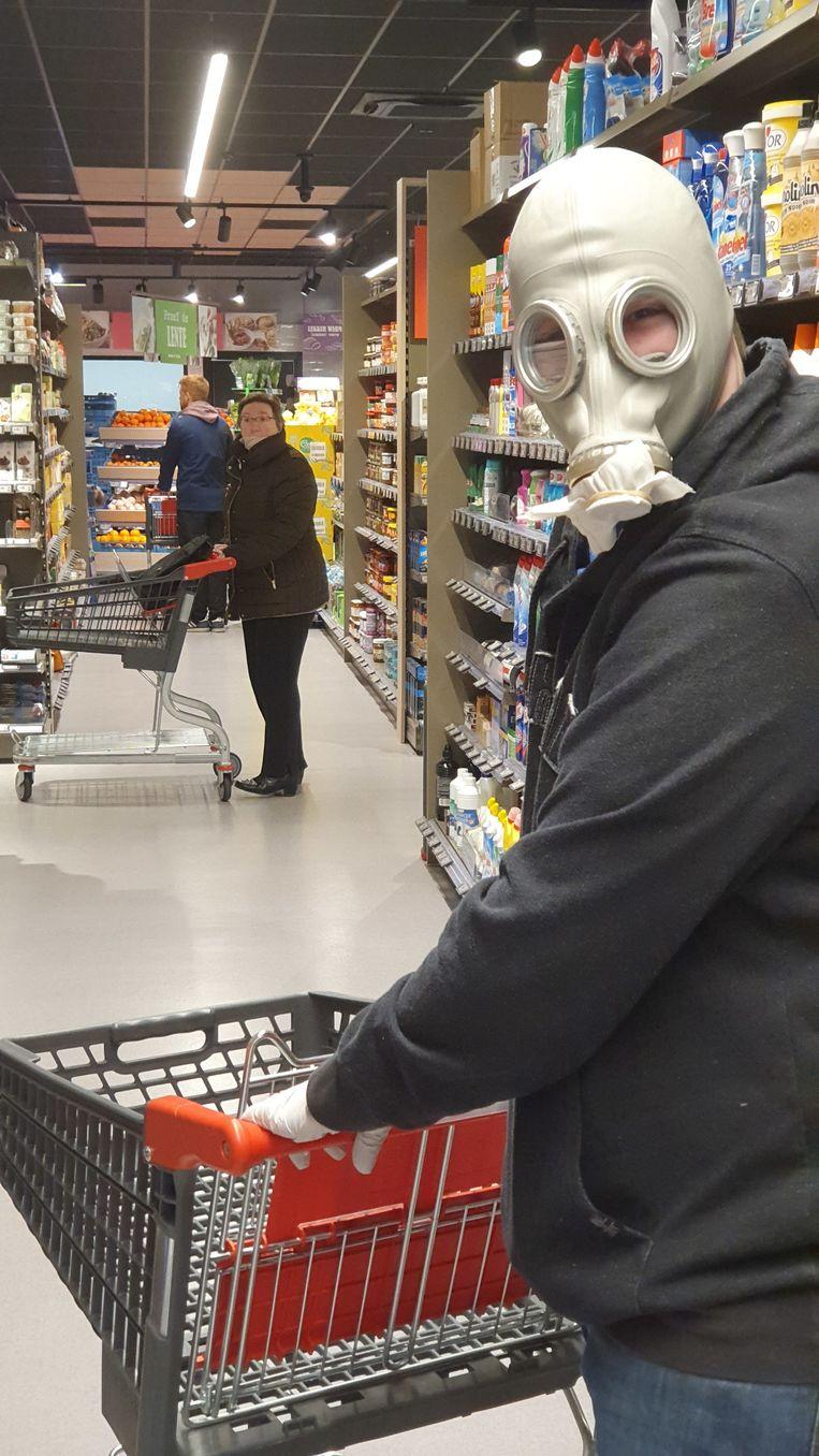 Ryan Vansteenkiste beschermt zich tegen het coronavirus met een gasmasker.