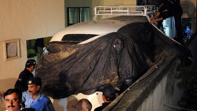 Pakistaanse agenten dekken het busje af waarmee de familie van Osama bin-Laden wordt vervoerd. Beeld afp