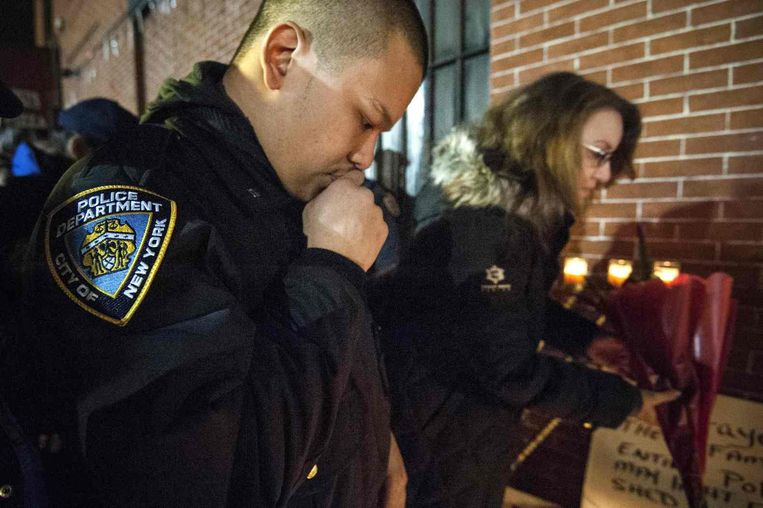 Een agent legt bloemen op de plek waar de twee agenten werden neergeschoten. Beeld reuters