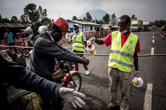 Op de weg van de Congolese stad Butembo en Goma wordt het verkeer tegengehouden tijdens een ebola-controlepunt. Motorrijders moeten daar verplicht hun handen desinfecteren.