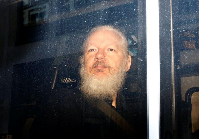 Julian Assange wordt na zijn arrestatie afgevoerd in een politiebus in Londen. Beeld Reuters