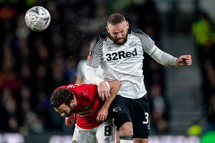 Wayne Rooney vecht een kopduel uit met Juan Mata (links).
