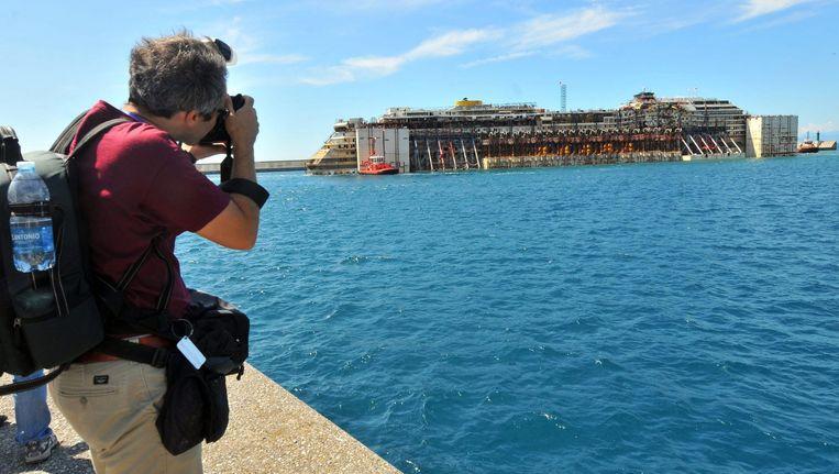 Een toerist fotografeert de Costa Concordia. Beeld epa