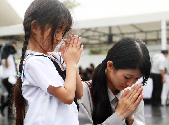 Moeder en dochter bidden voor de slachtoffers.