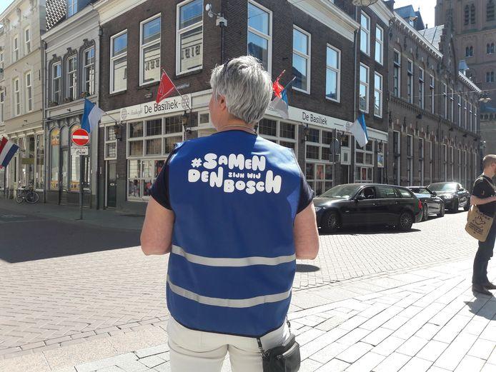 Een vrijwilliger vraagt in de Bossche binnenstad of mensen een veilige looprichting willen volgen.