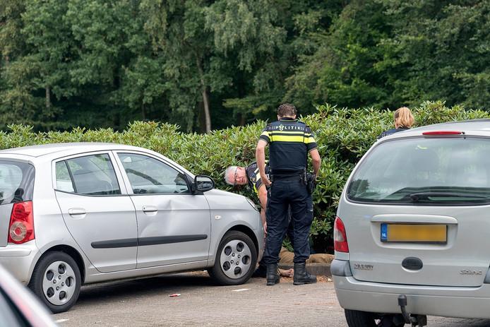 De gewonde man lag tussen de auto's en de struiken.